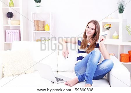 Young woman sitting with laptop on sofa and holding credit card in her hand, at home