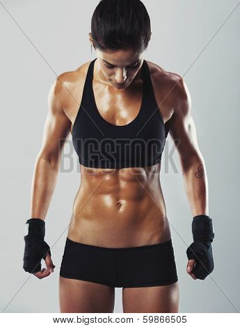 Portrait of attractive mixed race woman with muscular body looking down while standing on grey background. Fit and sexy young female bodybuilder posing. poster