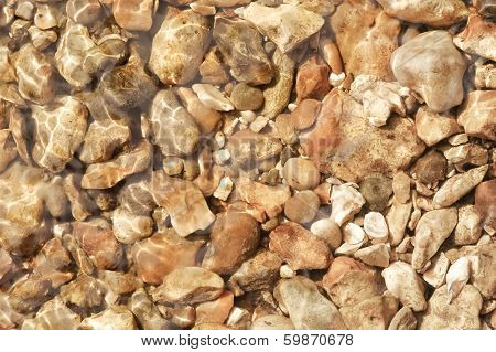 flat background of pebbles under flowing clear water poster
