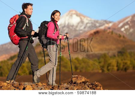 Hikers people hiking - healthy active lifestyle. Hiker people hiking in beautiful mountain nature landscape. Woman and man hikers walking during hike on volcano Teide, Tenerife, Canary Islands, Spain.