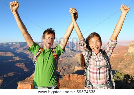 Happy people celebrating cheering in Grand Canyon. Young multiethnic couple on hiking travel excited and elated in Grand Canyon, south rim, Arizona, USA. Asian woman and Caucasian man. poster