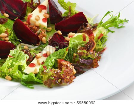 Fresh vegetarian gourmet salad with baked beetroot and cheese served on a white round plate. Isolated on white.