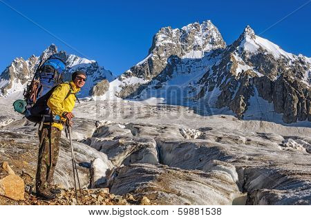 Hiker with a backpack on a glacier in the mountains of Georgia