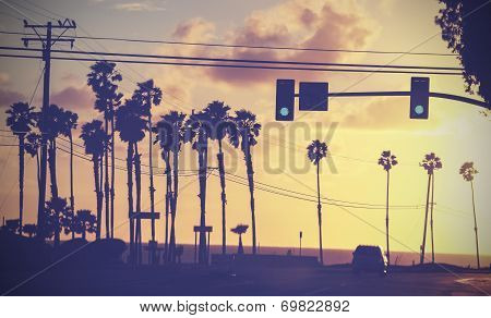 Vintage sunset picture of palms and poles on street against sun. poster