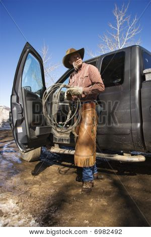 Man Wearing Cowboy Hat With Lariat And Truck