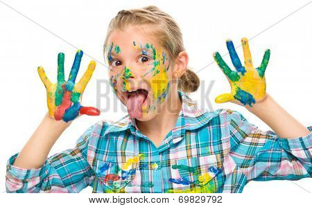 Portrait of a cute girl showing her hands painted in bright colors and sticking tongue out, isolated over white