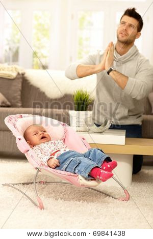 Young father praying for peace by crying baby.