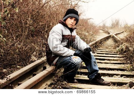 Young boy sitting on the railways