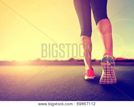 a woman with an athletic pair of legs going for a jog or run during sunrise or sunset - healthy lifestyle concept done with a retro vintage instagram like filter  poster