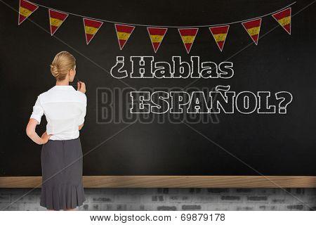 Thinking businesswoman against blackboard on wall, Do you speak Spanish?