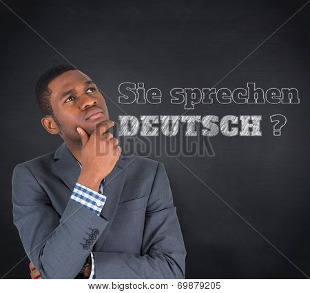 Composite image of young businessman thinking against blackboard, Do you speak German?