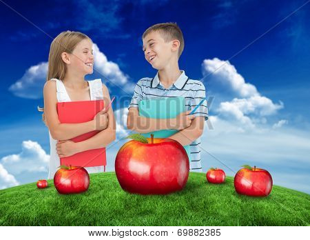 Smiling brother and sister holding their exercise books against green field under blue sky poster