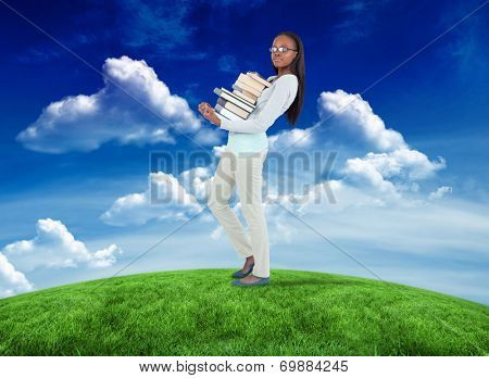 poster of Side view of young woman carrying a pile of books against green field under blue sky