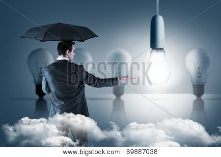 Businessman holding an umbrella with hand out against five light bulbs in a row with one lit up