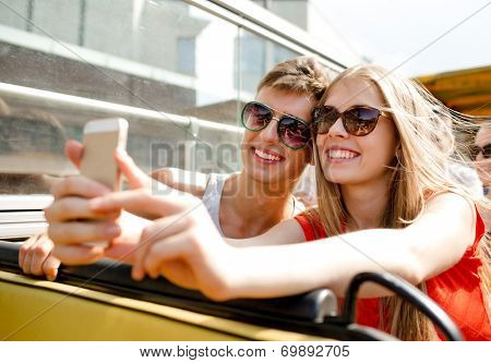 friendship, tourism, summer vacation, technology and people concept - smiling couple with smartphone traveling by tour bus and making selfie