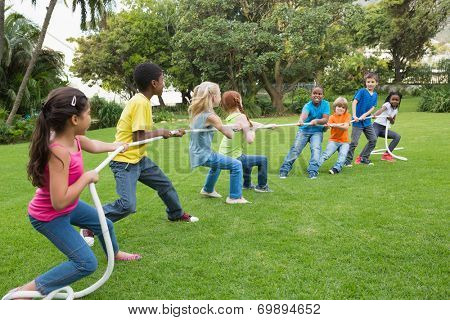 Cute pupils playing tug of war on the grass outside at the elementary school poster