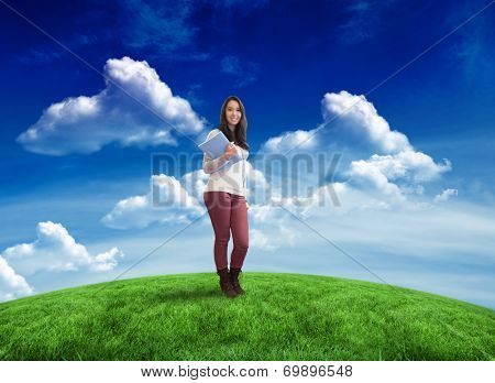 Smiling student holding textbook against green field under blue sky poster