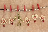 Wooden christmas decorations of star, tree and heart hanging on a pussy willow branch with mistletoe over old brown paper background. poster