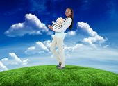Side view of young woman carrying a pile of books against green field under blue sky poster