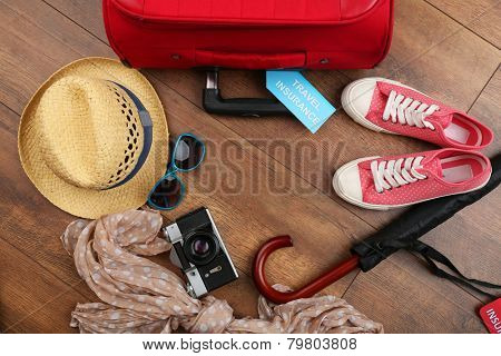 Suitcase and tourist stuff with inscription travel insurance on wooden background poster