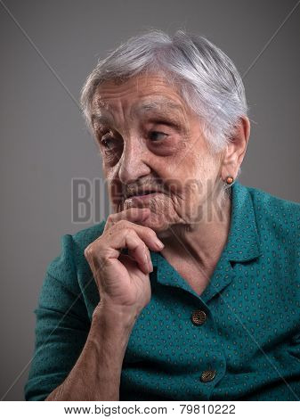Elderly Woman With Hand On Chin.