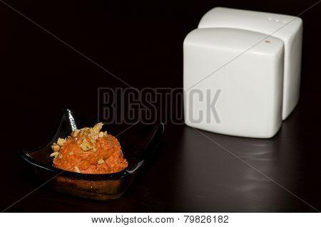 Dish Of Orange Paste Beside White Cruet
