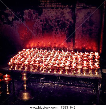 Burning candles in Buddhist temple - vintage effect. Lights oil candles - retro filter. Bodh Gaya Bihar India. Oil lamps enlighten. poster