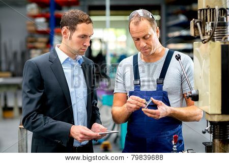 in the factory- young boss and worker in conversation poster