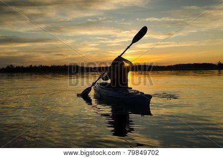 Woman Kayaks At Sunset
