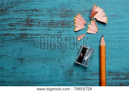 Pencil with sharpening shavings on color wooden background