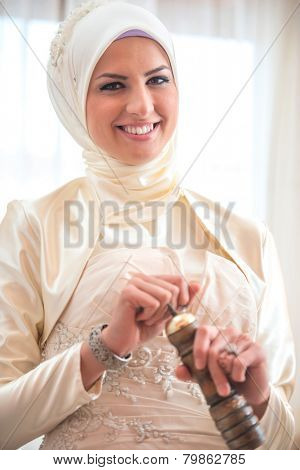 Smiling islamic girl grinding coffee in a hand mill poster
