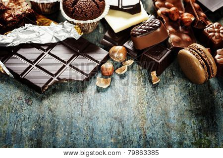An assortment of  white, dark, and milk chocolate with nuts, muffins, macaroons - on wooden background