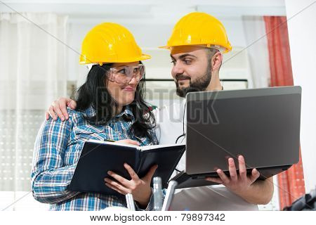 Craftsman and craftswoman posing together, with laptop and planner, selective focus