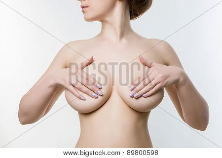 female breasts covered with hands, checking for breast disease,