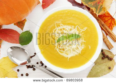 Pumpkin soup with autumn leaves, spices and a pumpkin