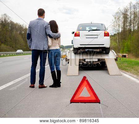 Couple near tow-truck picking up broken car
