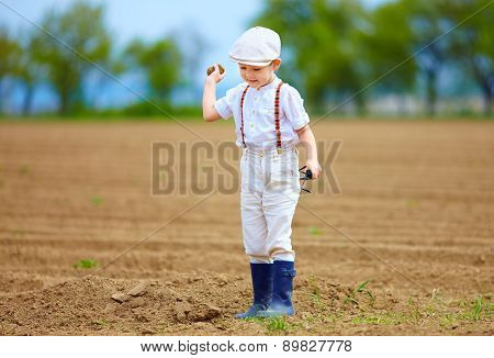 Cute Little Farmer On Spring Field, With Earth Clod In Hand