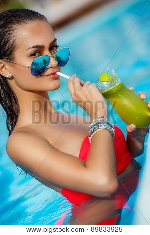 Elegant young woman in the pool with a cocktail.