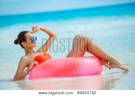 Beautiful woman with an inflatable life buoy on a tropical beach.
