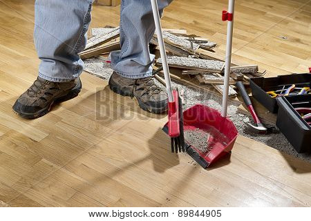 An unrecognizable person with a broom sweeping floor into dustpan.