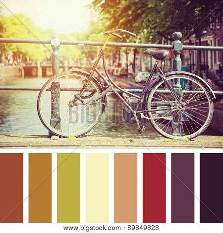 Bicycle on a bridge in sunlight, Amsterdam. In a colour palette with complimentary colour swatches.