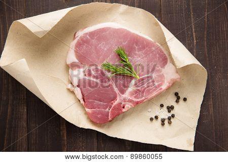 Raw Pork Chop Steak On Paper And Wooden Background