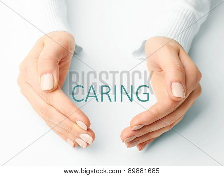Female hands with word caring on light background