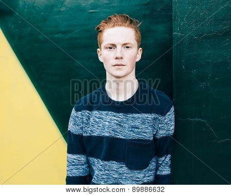 Young redhead man in a sweater and jeans standing next to green and yellow wall poster