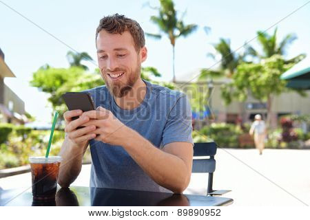 Man on cafe using smart phone app text messaging sms drinking iced coffee in summer. Handsome young casual man using smartphone smiling happy sitting outdoors. Urban male in his 20s.