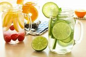 Detox water with various types of fresh fruit and vegetables in mason jars on a table poster