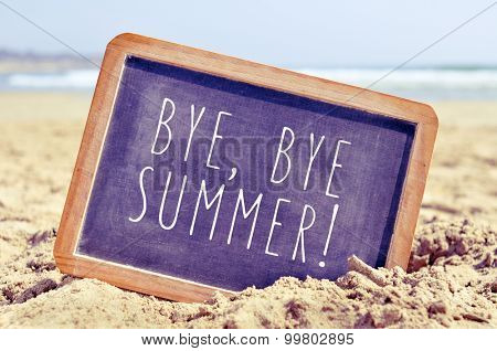 closeup of a chalkboard with the text bye, bye summer written in it, on the sand of a beach
