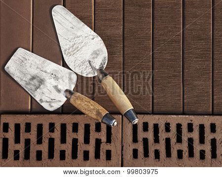 Construction's tools on brown clinker brick background. Brick masonry concept. Space for text.