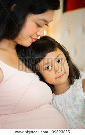 Portrait of Asian Pregnant Mother And Daughter