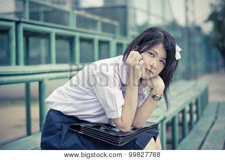 Shy Asian Thai Schoolgirl Student In High School Uniform Education Fashion Is Sitting On A Metal Sta
